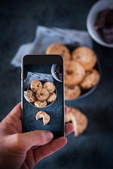 チョコレートとクッキーに携帯電話で写真を撮る人
