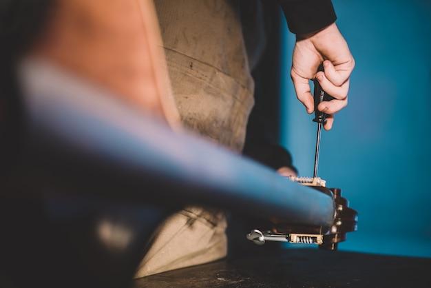 コントラバスを構築する職人の弦楽器製作者の手