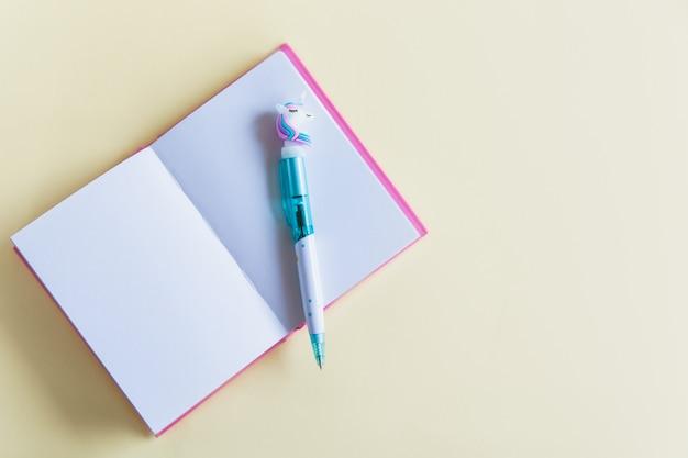 ノート、黄色のパステル調の背景に面白いユニコーンペンのピンクのノートブック。平らに置きます。上面図。コピースペース