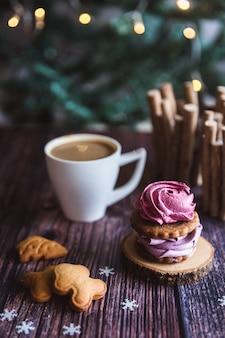 Домашний розовый и фиолетовый зефир в сахарной пудре с белой кружкой на деревянном