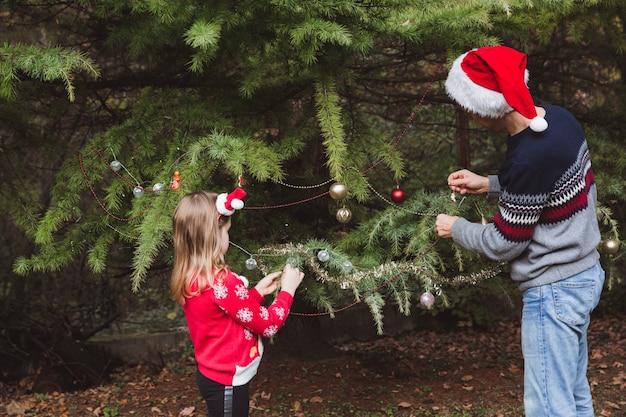 , отец в красной новогодней шапке и дочь в красном свитере украшают елку на улице во дворе дома перед праздниками