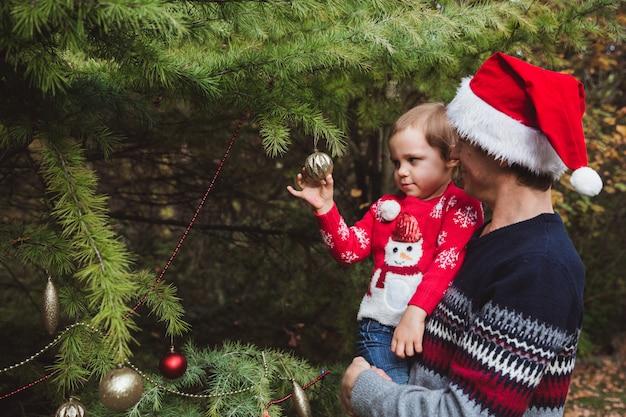 。赤いクリスマス帽子の父と休日前に家の庭で屋外のクリスマスツリーを飾る赤いセーターの娘