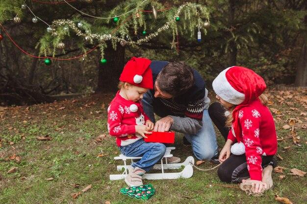 赤いクリスマス帽子の父は、家の庭で屋外のクリスマスツリーの近くの娘のためのプレゼントボックスを準備します。