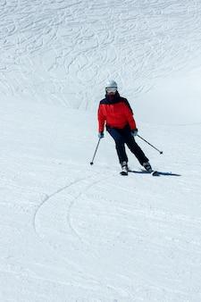 下り坂の女性スキーヤー。冬のスポーツレクリエーション活動
