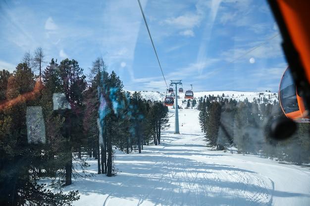 冬の雪に覆われた山々の背景の美しい景色の索道リフトのゴンドラキャビンからの眺め