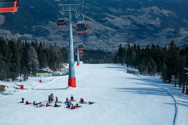 多くのスキーヤーやスノーボーダーがスキー場の斜面で休憩しています