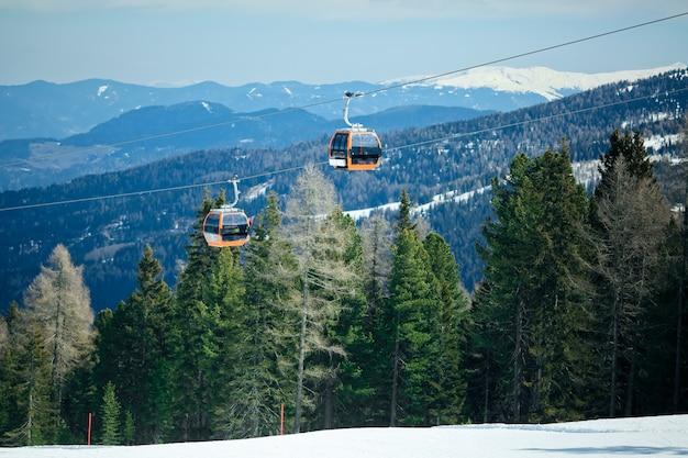 冬の雪に覆われた山の背景の美しい景色を持ち上げる索道のオレンジゴンドラキャビン
