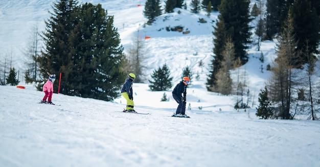 冬景色:子供たちのグループはスキーを習っています