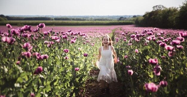 ライラックのケシの花のフィールドで孤独に歩いて白いドレスを着た髪の長いかわいい女の子