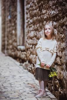 晴れた春の日に黄色の花で旧市街に立っているトレンドの服の愛らしい少女