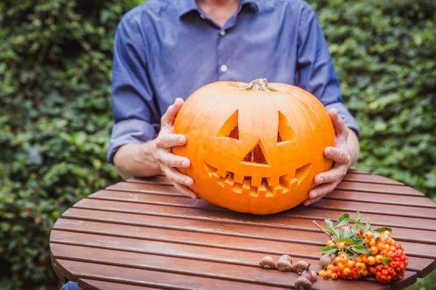 ハロウィーンの木製テーブルに大きなカボチャを彫刻男