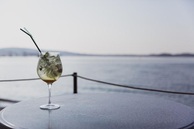 モヒートの冷たいガラスは海の近くのテーブルの上に立つ