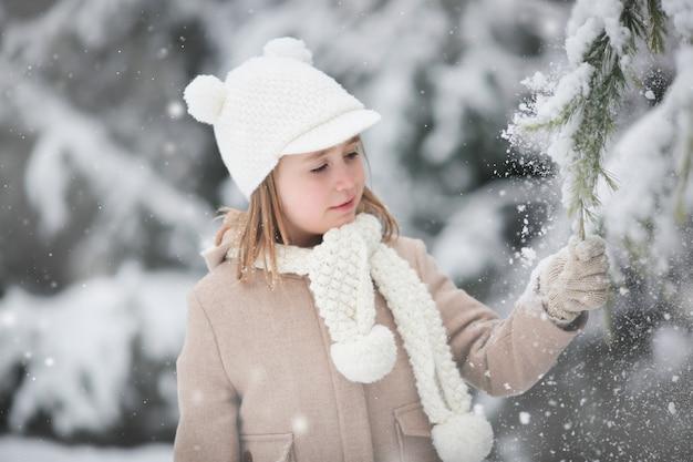 小さな女の子は自分でモミの木から雪を振ります。