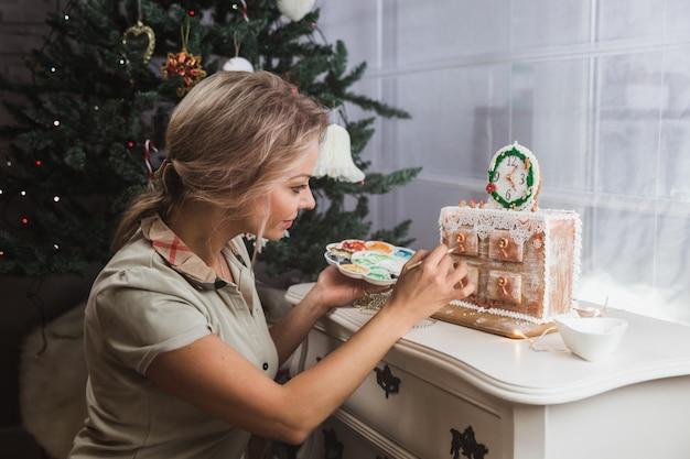 女性は自宅でジンジャークッキークリスマスのチェストを飾ります。女性は蜂蜜のジンジャーブレッドクッキーに塗料を描画します