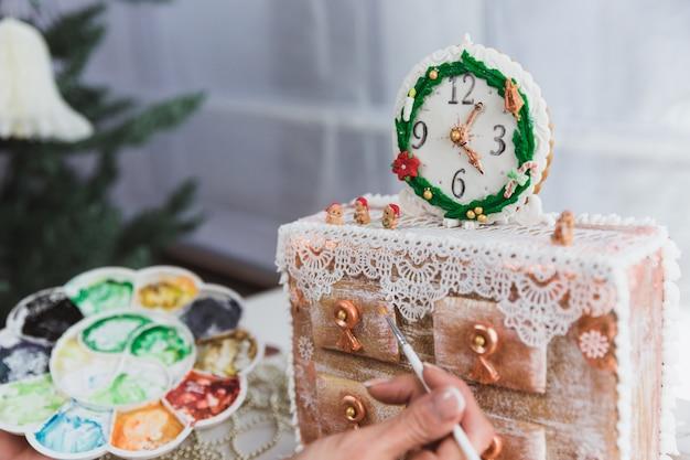 女性は自宅でジンジャークッキークリスマスのチェストを飾ります。女性は、蜂蜜のジンジャーブレッドクッキーに絵の具を描きます。閉じる