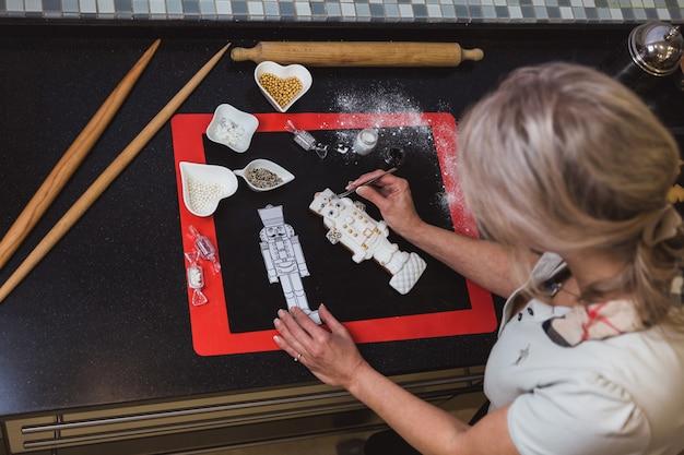 Женщина украшает рождественские пряники сахарной глазурью с глазурью. рождественский подарок, домашние пряники