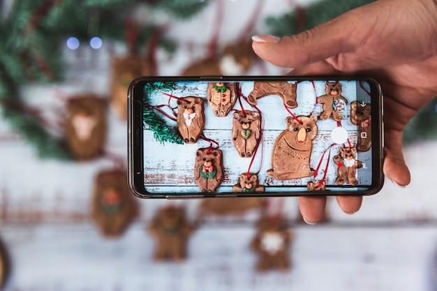 女性は電話で写真を撮る手作りのクリスマスジンジャーブレッドベアファミリークッキーと美しい木製の砂糖フロスティング平置き