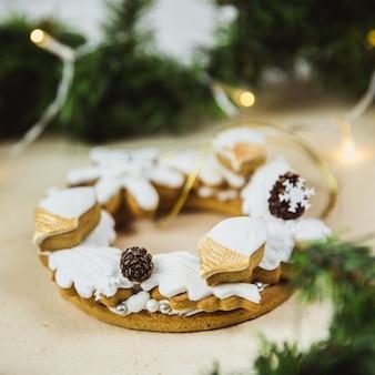 Рождественский венок с печеньем. новогодний подарок имбирного пряника. рождественская елка украшена огнями