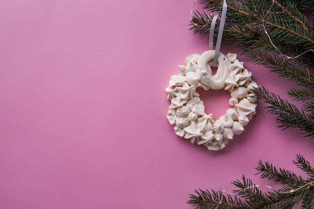 ピンク色のモミの枝にクリスマスメレンゲの花輪。平置き