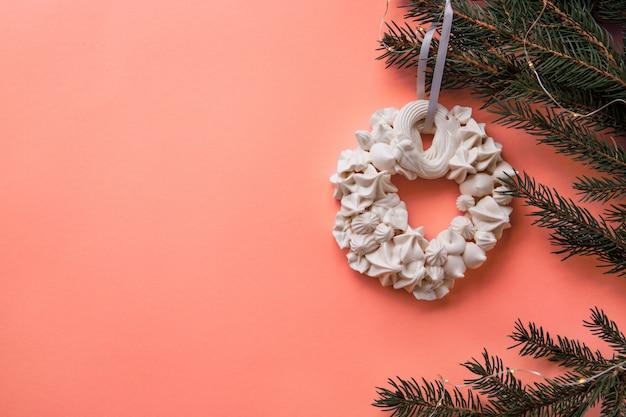 生きているサンゴ色のモミの枝にクリスマスメレンゲの花輪。