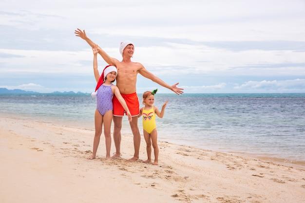 Молодой дружный семейный отец и две дочери счастливы в летнее рождество на пляже