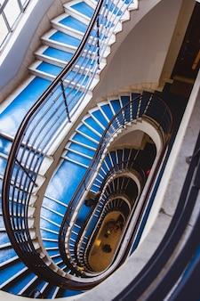 Старая голубая винтовая лестница, винтовая лестница внутри старого дома в будапеште, венгрии.
