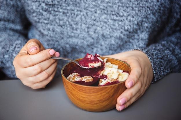 アサイスムージー、グラノーラ、種子、木製のボウルに新鮮な果物、灰色のテーブルの上の女性の手