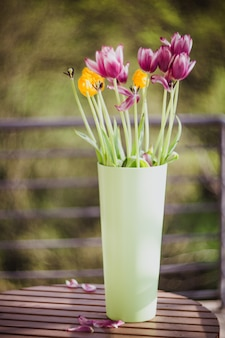外の木製のテーブルの上の緑の花瓶の美しい紫と黄色のチューリップ。