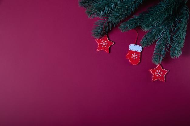 クリスマスの組成物。赤いクリスマスの木製装飾、赤の背景にモミの木の枝。