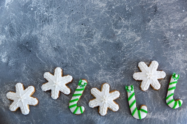 手描きのクリスマスジンジャーブレッドの緑と白のキャンディー杖と美しい灰色の背景に雪の結晶。カードのコンセプト。上面図。平干し。