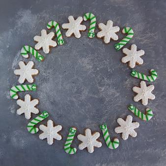 手描きのクリスマスジンジャーブレッドの緑と白のキャンディー杖と美しい灰色の背景に雪の結晶。