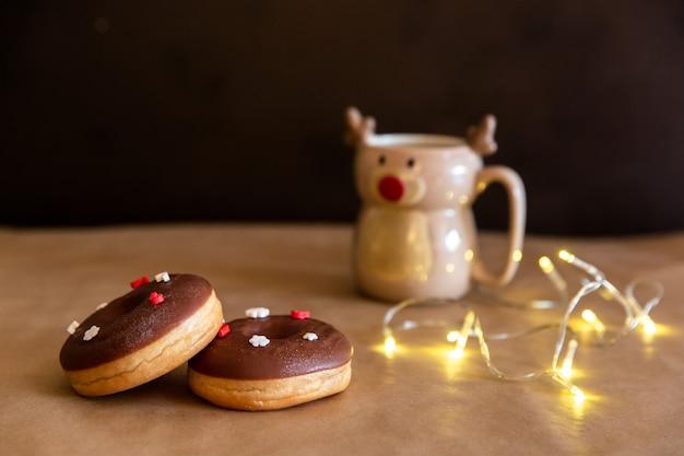 チョコレートドーナツとクリスマスの朝食用のテーブルには、鹿のマグカップでホットココアと赤と白のスプリンクルが飾られて