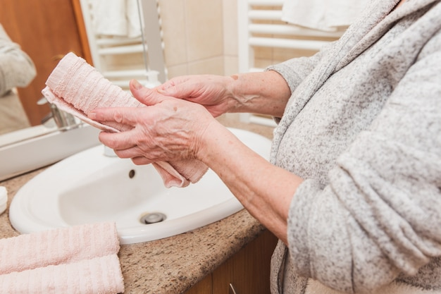 年配の女性は朝の時間に浴室でタオルで彼女の手を拭く
