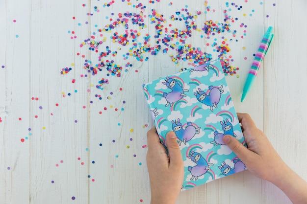 ラマユニコーンと虹のノートを保持している女の子の手