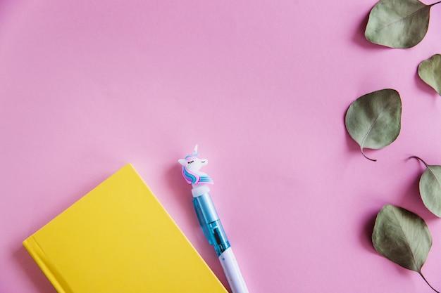 ピンクのパステル調の背景に黄色のノート、面白いユニコーンペン、緑のユーカリのノートを残します。平らに置きます。上面図。コピースペース
