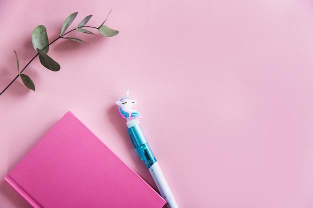ピンクのパステル調の背景にピンクのノート、面白いユニコーンペン、緑のユーカリのノートブックを残します。平らに置きます。上面図。コピースペース