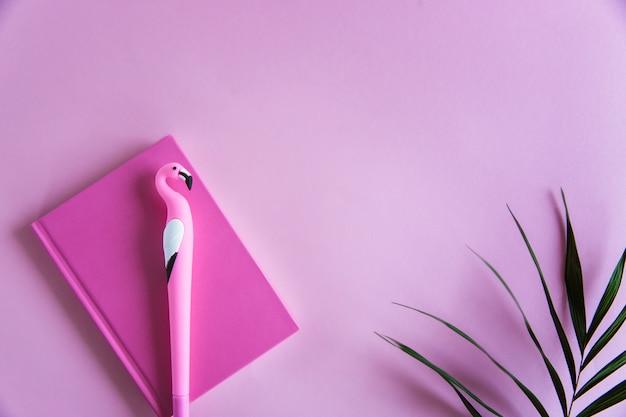 ピンクのパステル調の背景にノート、面白いフラミンゴペン、緑のヤシのピンクのノートブックを残します。平らに置きます。上面図。コピースペース