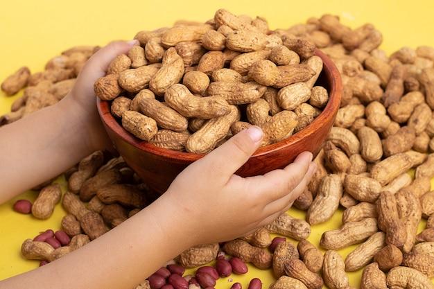 皮が付いたままのピーナッツと木製のボウルを保持している女の子