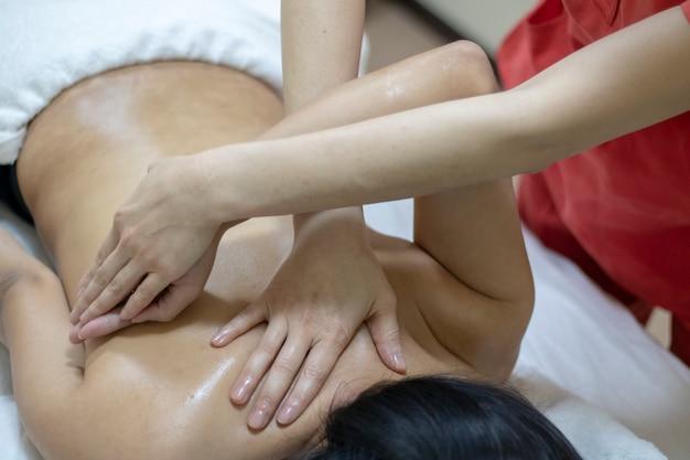 スパサロンで女性の体にマッサージを行うマッサージ師