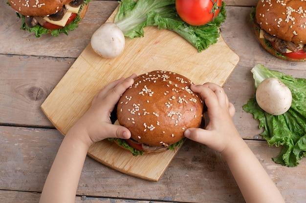 Ребенок держит свежеприготовленный грибной бургер
