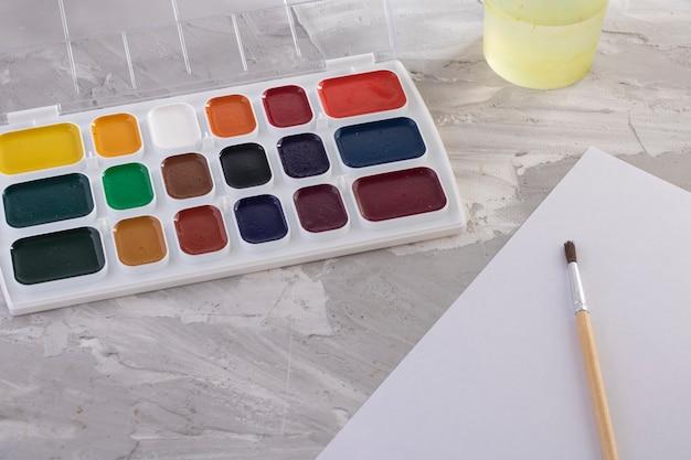 Грязные кисти с красками и бумагой, вода на сером столе
