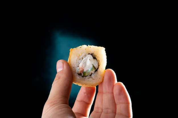 寿司ロール、コピー領域を持っている手。すぐに食べられる食事