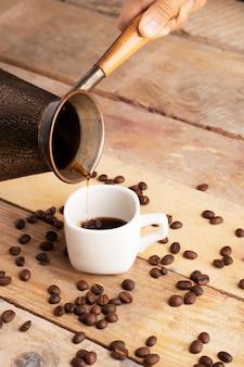 Вертикальное фото разлива кофе в чашку