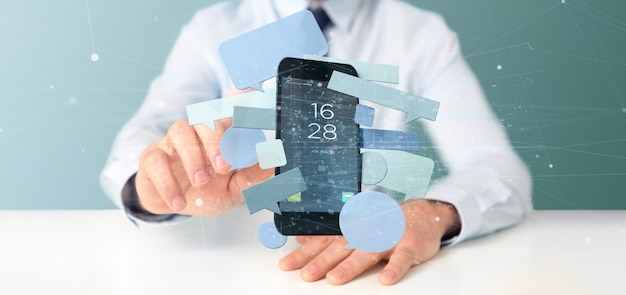 スマートフォンを囲むメッセージの泡を保持している実業家