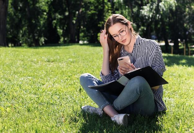 学生の女の子は公園の芝生の上に座っている彼女の手の中のフォルダーと彼女のスマートフォンに見える