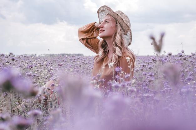 Красивая молодая беременная женщина в шляпе в сиреневом поле. цветущие цветы
