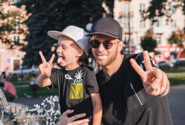 幸せなお父さんと息子の平和を見せて。散歩に彼の息子を持つ若い父親。