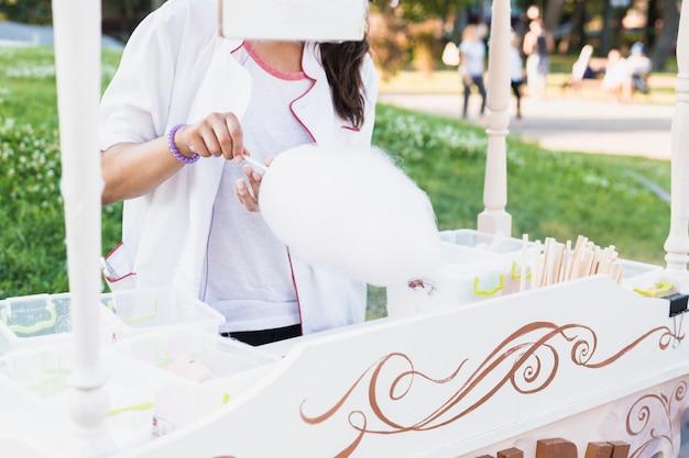 女性は公園で夏に甘いコットンウールを作る