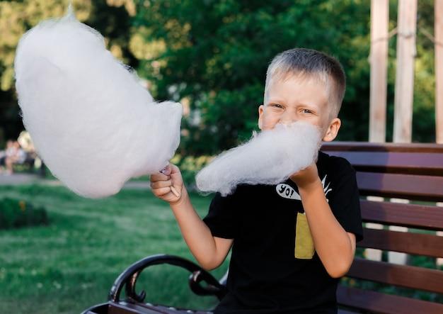 Мальчик ест сладкую вату из липкого сахарного песка, сидя на скамейке в парке
