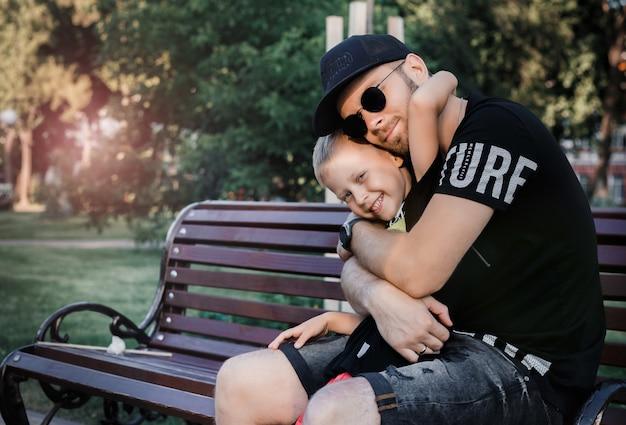 若いお父さんと息子が公園の路上でハグします。散歩に彼の息子を持つ若い父親。